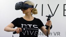A woman checks a pair of Vive Virtual Reality goggles, produced by Taiwan's HTC, during the Gamescom 2015 fair in Cologne